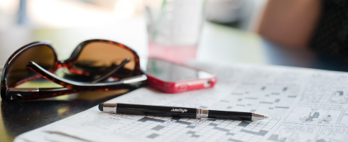 jukestyle stylus extended to pen on a newspaper crossword.